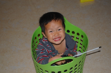 Roy, controlling a flashing Chinese remote-controlled car in a laundry basket